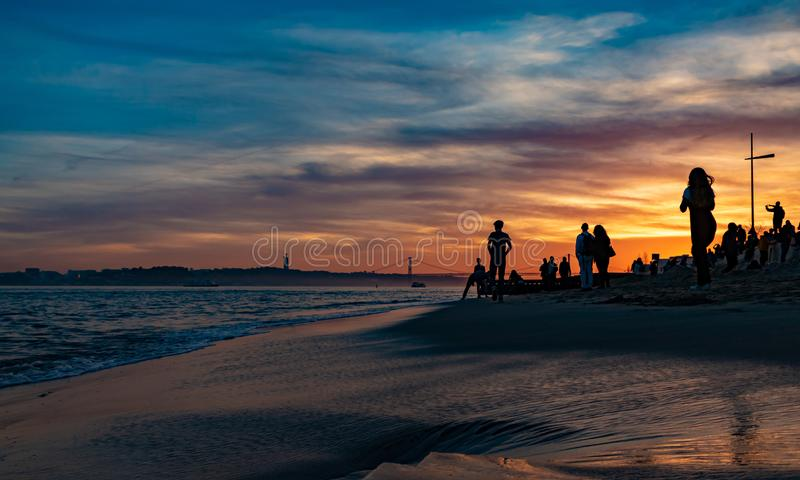 Sunset photo taken in prca de comercio, Lisbon. Beautiful dark blue sky with dark clouds, blue water and wet sand on the bank. stock photos