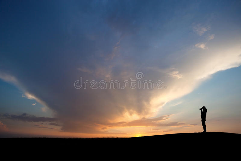 Sunset photographer. In sunset sky on hill stock photo