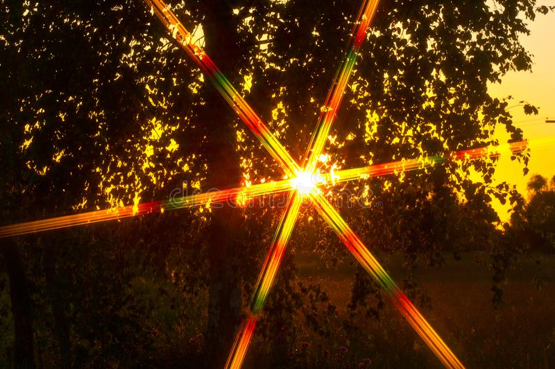 Sunset and physics. Optical phenomena. Observed optical phenomena. The picture was taken using a diffraction filter stock image