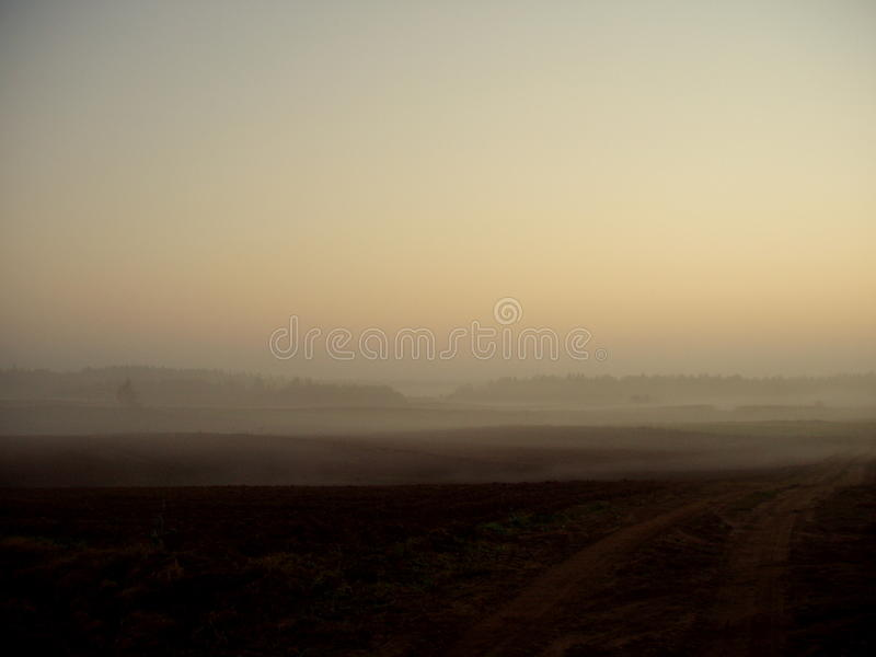 SUnset. This picture was taken early November in Poland in the Podlachia area. We see deserted fields and meadows with lots of fog. A picture captures a moment stock image