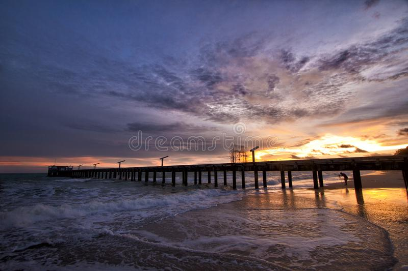 Sunset Pier in Rayong Thailand. Photographer, photography, sand, beacj, waves, ocean, sea, reflections, golden, yellow, purple, sky, blue, hour, hoir stock images