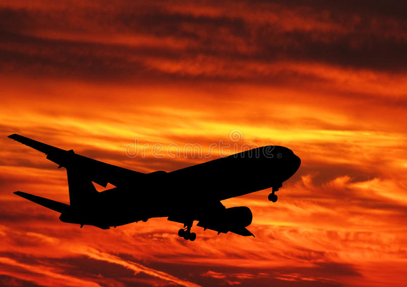 Sunset and plane. An amazing sunset sky and the silhouette of an air-plane while taking off stock images
