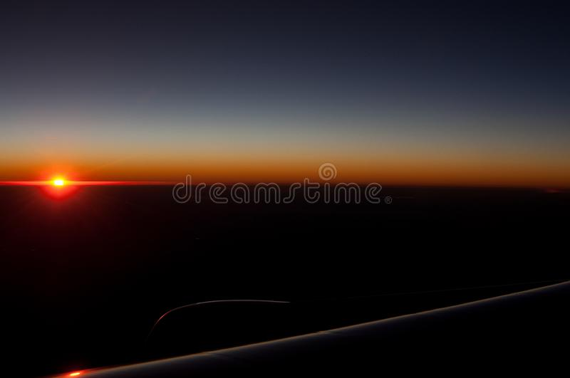 Sunset in plane with wing`s silhouette. Minimalism sunset in plane with wing`s silhouette stock photo