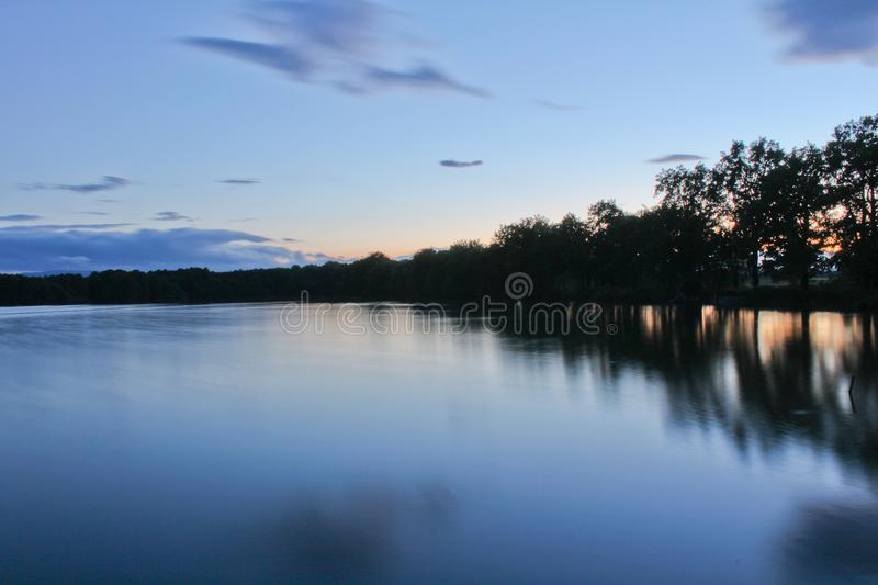Sunset on pond with trees silhouette and orange sky, long exposure, Czech landscape royalty free stock image