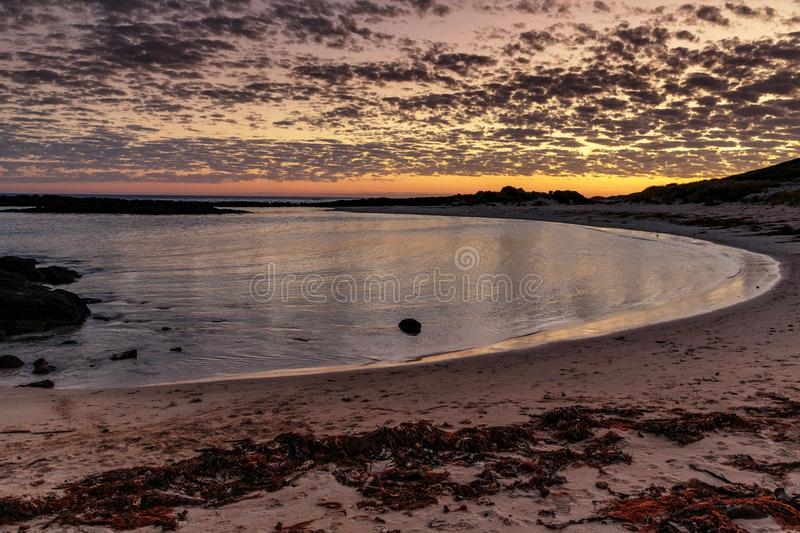Sunset at Port Fairy, Great Ocean Road, Victoria, Australia. Sun setting with a dappled sky and calm water. Open bay and sand dunes royalty free stock image
