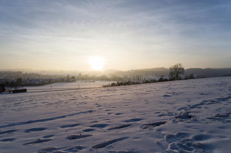 Sunset in purple shimmering winter landscape with snow, Amstetten, Germany. Sunset in purple shimmering winter landscape with snow - winter landscape with snow royalty free stock image