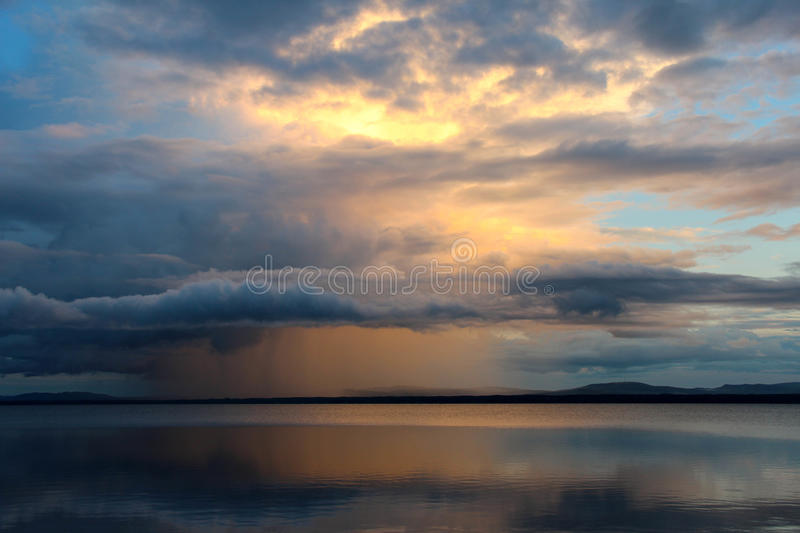 Sunset and rain clouds over Orsa lake, Sweden. royalty free stock photos