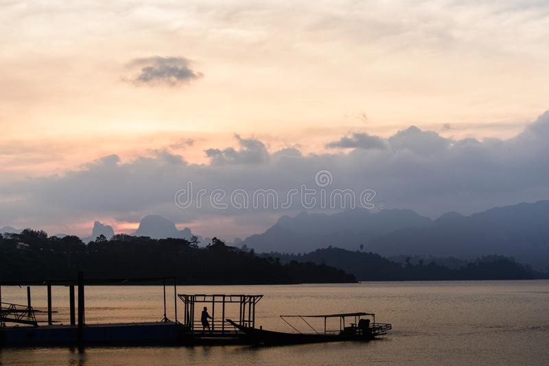 Sunset in lake with Siluate man and boat. Sunset in Ratchapapa dam at Thailand with A man and boat siluate royalty free stock image
