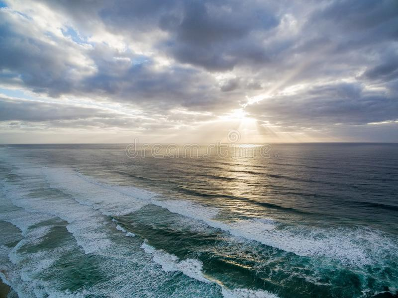 Sunset rays over ocean waves. Sunset rays over ocean waves under moody sky royalty free stock image