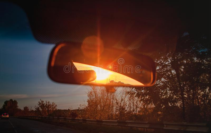 Sunset red sunbeams in a salon inside rearview mirror of a car. Close-up, blur.  stock photos