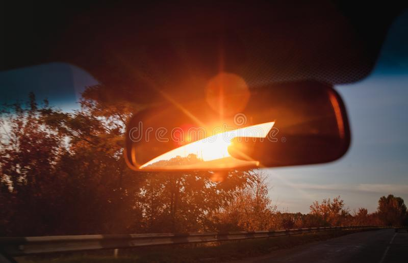 Sunset red sunbeams in a salon inside rearview mirror of a car. Close-up, blur.  royalty free stock photo