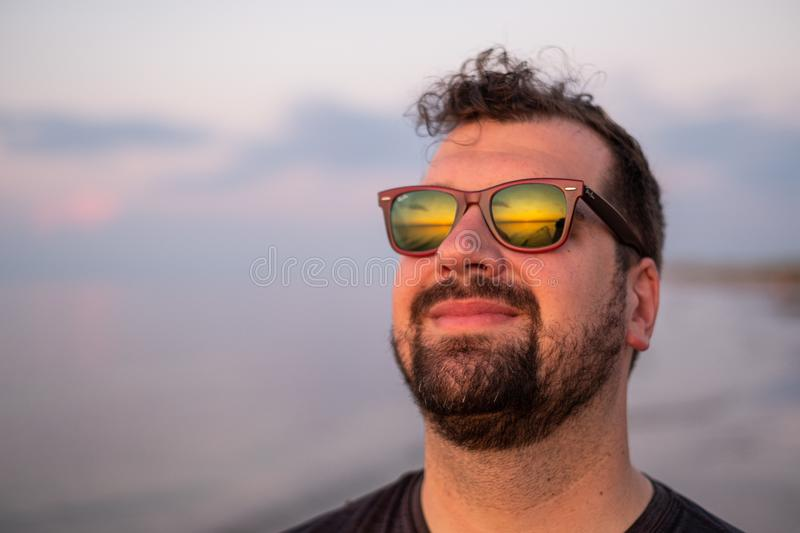 Sunset reflected in a man`s sunglasses stock photo