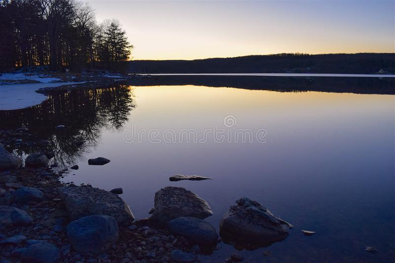 Sunset reflecting in calm waters stock photos