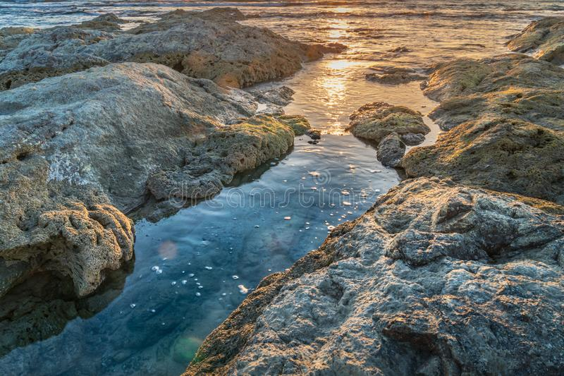 Sunset reflecting long rocky areas of the coastline. With golden light on blue water stock photography