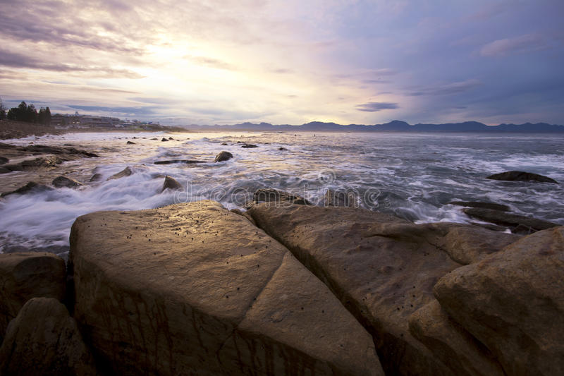 Sunset reflecting off ocean and rocks stock photography
