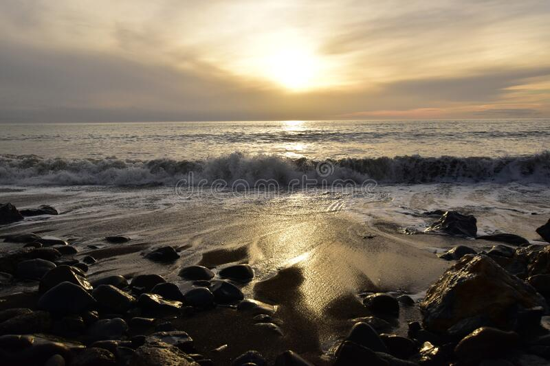 A sunset reflecting in the sea water with big waves in the frontA sunset reflecting in the sea water with big waves in the front stock photography