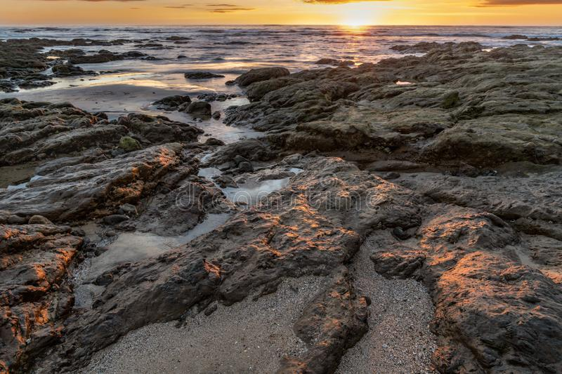Sunset reflection on rocky coastline. Sunset reflection on coastline on Costa Rican beach stock photo
