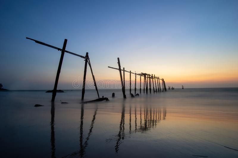 Sunset and reflections from the sea, decaying wooden bridges, Khao Pi Lai Phang Nga beach, Thailand.  royalty free stock photography