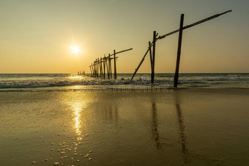 Sunset and reflections from the sea, decaying wooden bridges, Khao Pi Lai Phang Nga beach, Thailand.  stock photography