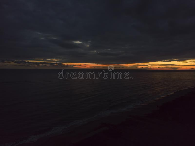 At sunset a relaxing flight over the ocean with a dramatic sky and the night ahead stock image