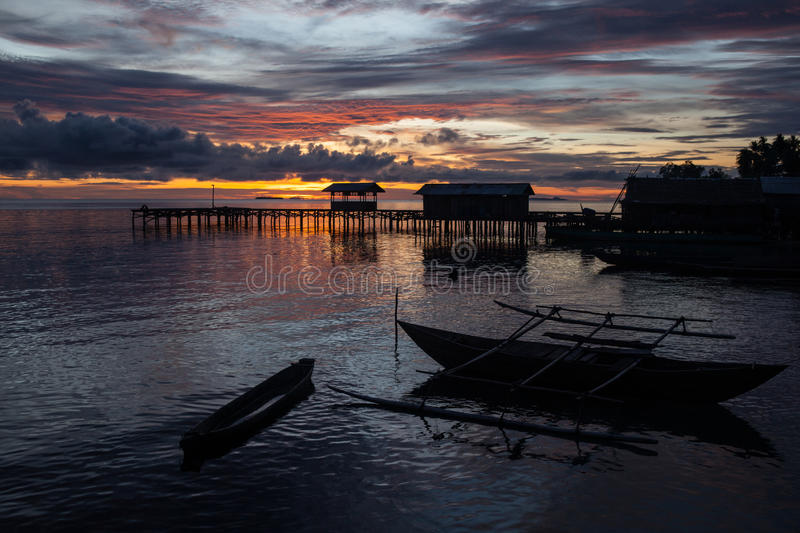 Sunset and Remote Village in Raja Ampat. A beautiful sunset silhouettes a pier and canoes in Raja Ampat, Indonesia. This remote region is the heart of the Coral royalty free stock photo