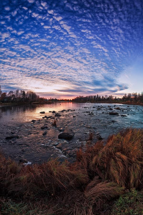Sunset By The River Bend. The autumn sun sets behind the horizon over the river bend in the Northern Finland. The setting sun emphasized the colors of the autumn stock images