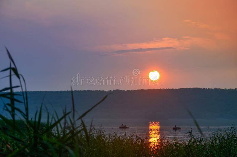Sunset on the river. Fishermen in boats on the river fishing at sunset. Sunset on the river and green meadow. Fishermen in boats on the river fishing at sunset stock photos