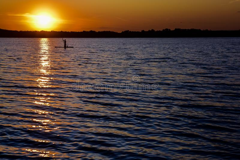 Sunset on the river, surfers in the evening on the calm water. Sunset on the big river, surfers in the evening on the calm water royalty free stock photos