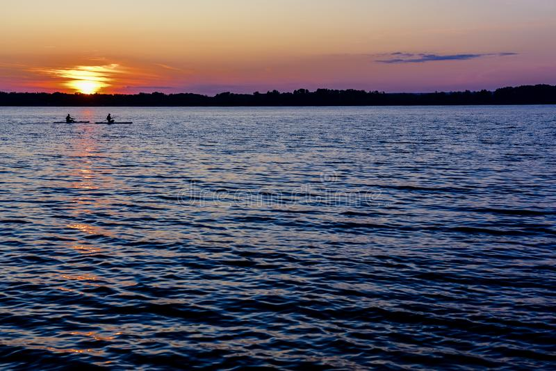 Sunset on the river, surfers in the evening on the calm water. Sunset on the big river, surfers in the evening on the calm water stock photography