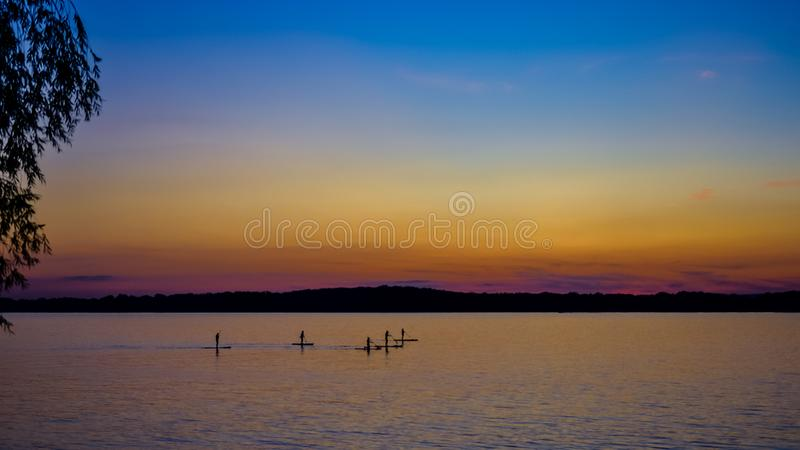 Sunset on the river, surfers in the evening on the calm water. Sunset on the big river, surfers in the evening on the calm water royalty free stock photography
