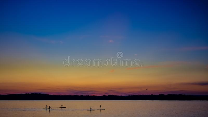 Sunset on the river, surfers in the evening on the calm water. Sunset on the big river, surfers in the evening on the calm water royalty free stock images