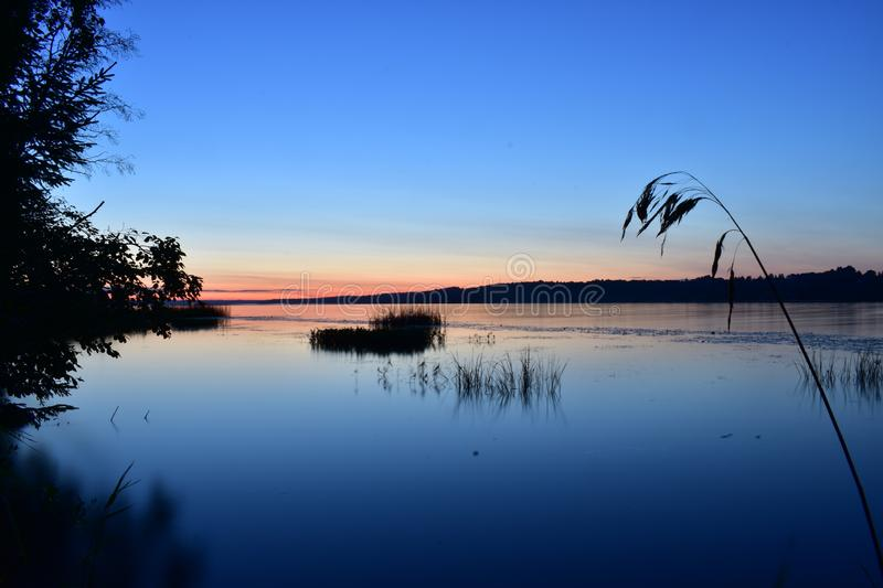 Sunset on the river turns into dawn, blue sky reflected in the water stock photos