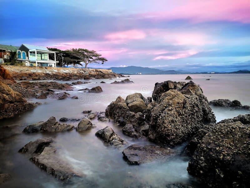 Sunset on rock beach stock image