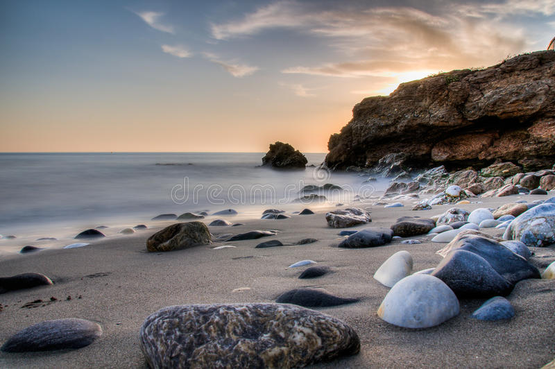 Sunset rocks on beach. A colorful sunset on Praia da Ursa beach at Cabo da Roca, Portugal, with large rocks and boulders silhouetted against the sky stock photography