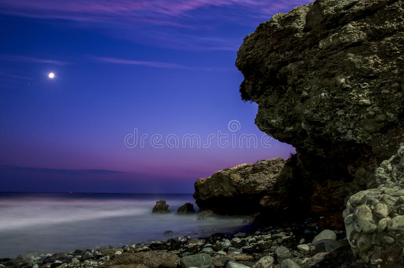 Sunset rocks on beach. A colorful sunset on Praia da Ursa beach at Cabo da Roca, Portugal, with large rocks and boulders silhouetted against the sky royalty free stock photography
