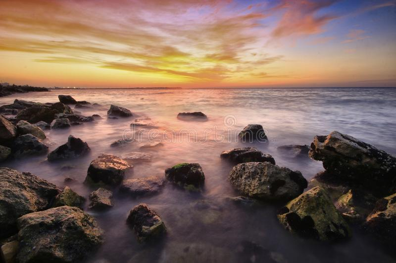 Sunset with rocks on the seashore. Sunset with the rocks on the beach in a day filled with clouds royalty free stock photo