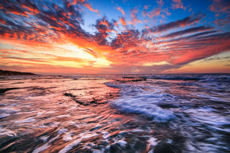 Sunset with rocks on the seashore. Sunset with the rocks on the beach in a day filled with clouds stock photo