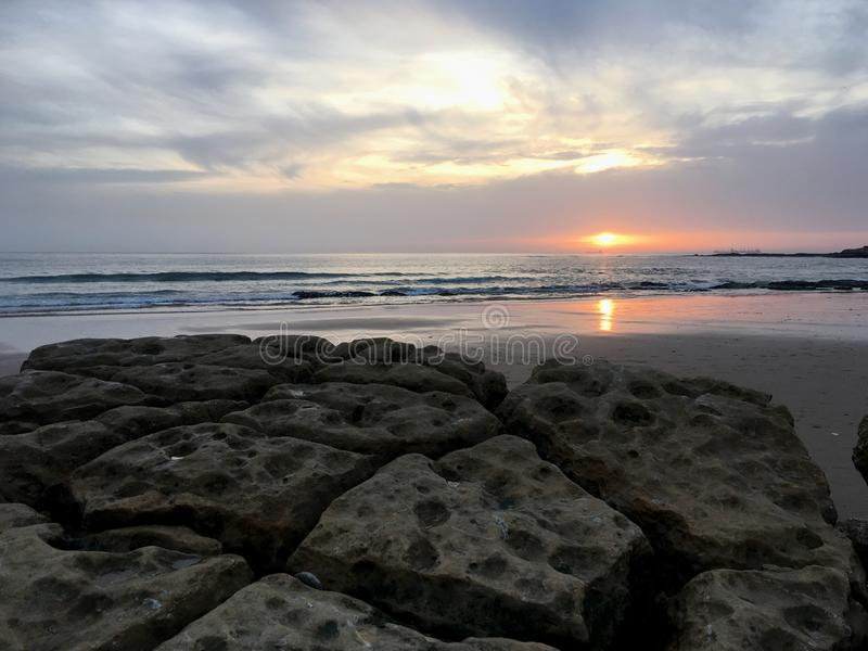 Sunset on a rocky beach, Carcavelos, Portugal, Europe. Beautiful cloudy sunset during low tide on a quiet rocky beach in Carcavelos, Portugal, Europe stock photo