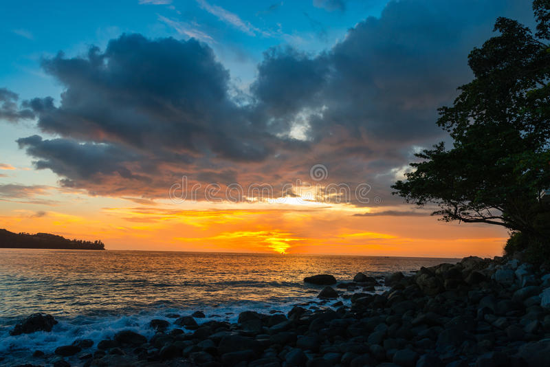 Sunset on a rocky coastal beach with orange and blue clouds royalty free stock photography