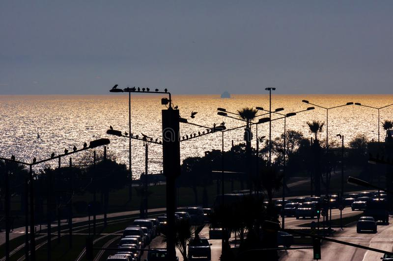 Sunset`s coming in Izmir Turkey. A main street of Izmir with many street lights, in backlight. At background there is the panorama of the Aegean sea in the stock photography