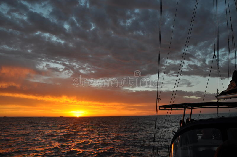 Sunset Sail Glows Orange over the Indian Ocean: Australia. Sunset sail out of Fremantle, Western Australia with the orange sunset and a cloudy sky over the stock photography