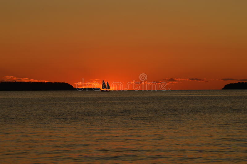 Sunset. Sailboat sailing across the water as the sun begins to set stock images
