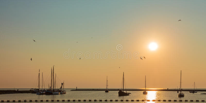 Sunset with sailing boats in Friesland royalty free stock photography