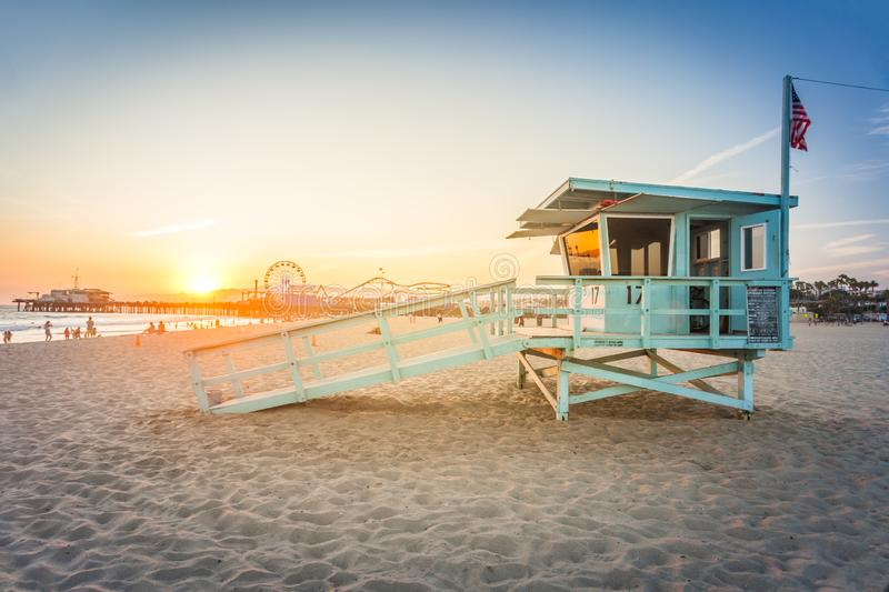 Sunset in Santa Monica. Sunset on Santa Monica beach with rescue cabin and amusement park on the background royalty free stock photos