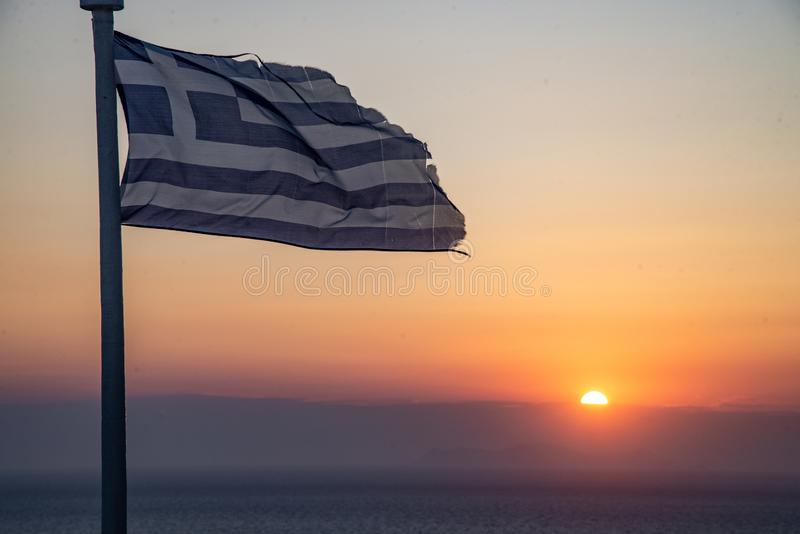 The sunset of Santorini volcanic island of the Aegean Sea in Greece. The sun behind the horizon line, with a Greek flag foreground. The most romantic place in stock photography
