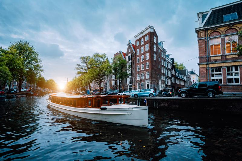 Sunset scene in Amsterdam city. Great Tourist boat on the famous Dutch canal floating tilted houses. Colorful evening stock image