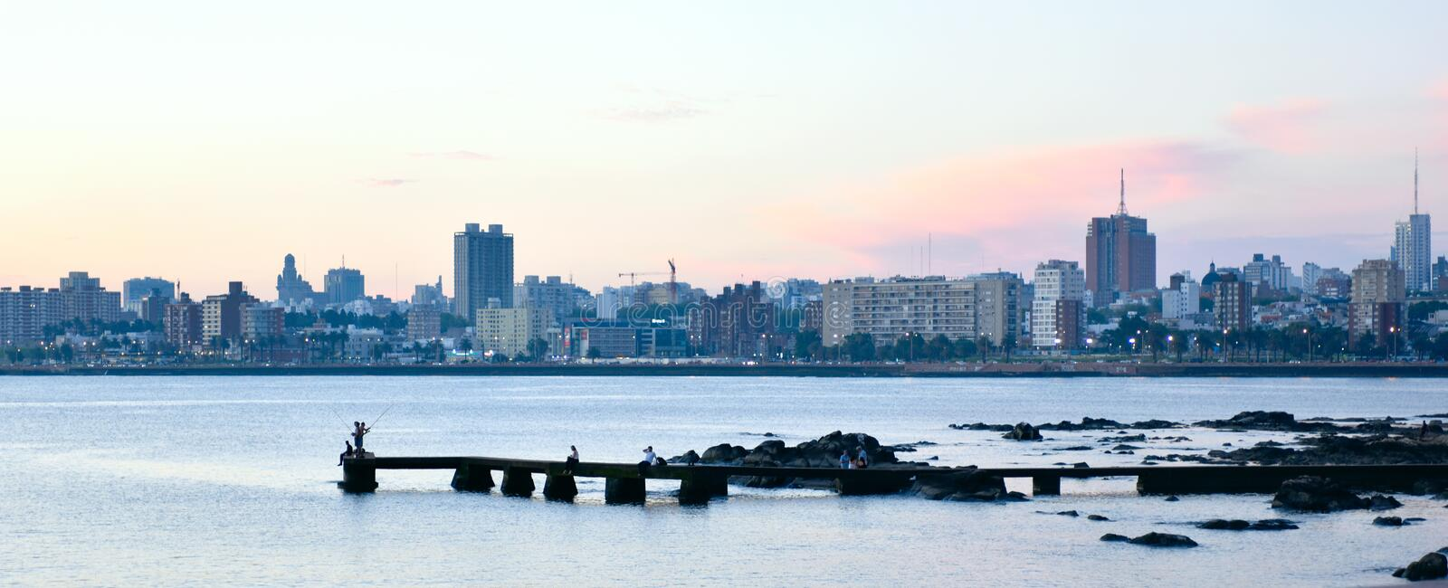 Sunset scene of beach and skyline in Montevideo, Uruguay. Montevideo, Uruguay - February 20, 2017: Sunset scene of beach and skyline at background stock photos