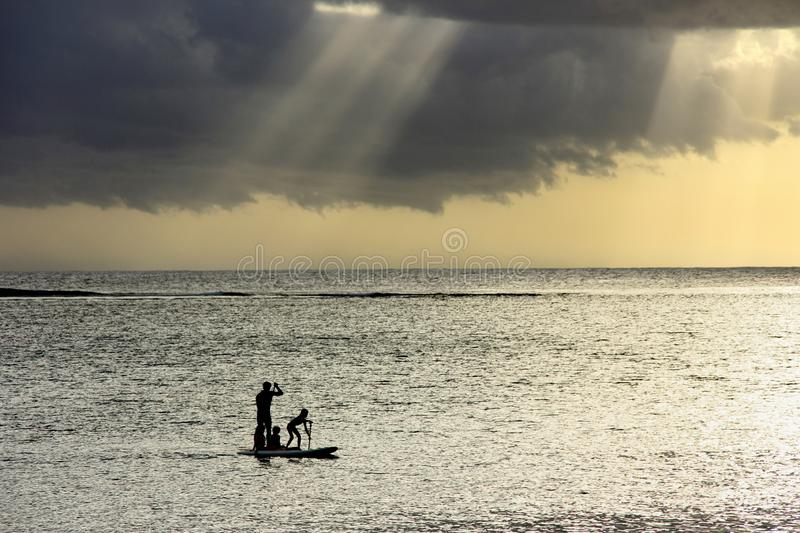 Sunset scene on coming thunderstorm background. A father with three children are paddling on two boards stock photography