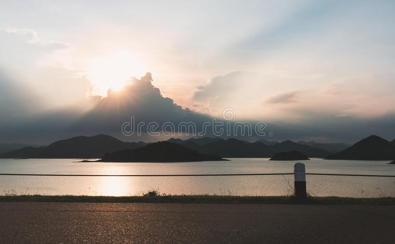 Sunset scene on dam. Low key tone of sunset scene with cloudy sky and black mountain range under clouds looking from coast stock photos