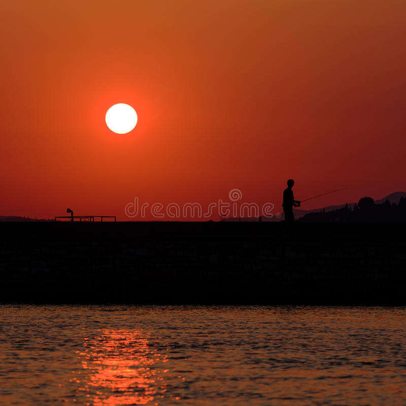 Download Sunset Scene With Fisherman Stock Image - Image: 26804223